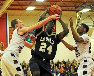 La Salle's Shawn Witherspoon drives to the net, while Lower Merion's Corey Shermen, left, and Steve Pendleton defend Saturday. Montgomery Media staff photo / SCOTT ROMAN