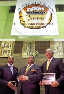 Under the banner that announces that the Chester High gym is now the Fred J. Pickett Jr. Memorial Gym stand, from left, state Rep. Thaddeus Kirkland, D-159, of Chester; Chester Upland District Superintendent Greg Shannon and Chester Mayor John Linder. The memory of the longtime Chester coach who died in October was honored in a ceremony to rename the gym prior to the Clippers' game against Penn Wood. (Robert J Gurecki)