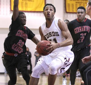 Haverford School's Lamar Stevens, center, tries to split the Germantown Academy defense of Devon Goodman, left, and Evan-Eric Longino in Tuesday's game. The Fords let a late lead slip away in a 60-57 loss. (Robert J. Gurecki)