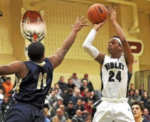 Ridley's Julian Wing, right, rises up for a shot over West Chester Rustin;s Tyler Blake during the Green Raiders' 68-55 victory in a District One Class AAAA opening-round game Friday night. (Eric Hartline)