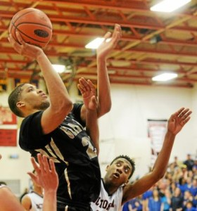 Glen Mills' Anthony Johnson, left, goes up for a layup over Octorara's Levi Worthington during the District One Class AAA championship game Saturday. Worthington and the Braves claimed the district title with an 80-54 victory. (Tom Kelly IV)